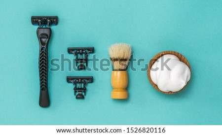 Black razor with two replacement blades and a shaving brush for shaving on a blue background. Set for care of a man's face. Flat lay.