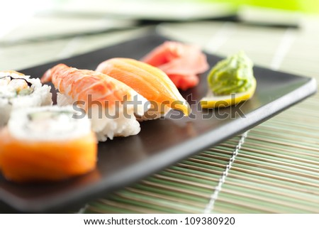 Black rectangle plate with sushi rolls, isolated on white