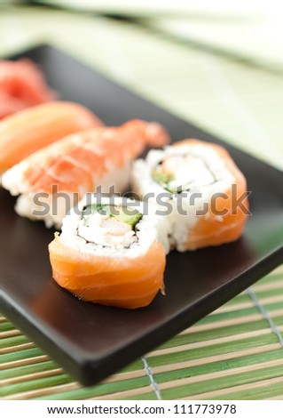 Black rectangle plate with sushi rolls, isolated on white background