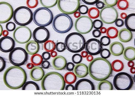 Black, red and gre hydraulic and pneumatic o-ring seals of different sizes scattered a white background. Rubber rings. Sealing gaskets for hydraulic joints. Rubber sealing rings for plumbing. Top view