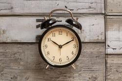 Black retro alarm clock on wooden background