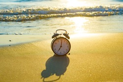 black retro alarm clock stands on the sand against the background of the sea, 7 am concept of get up early