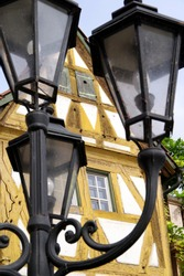 black retro cast iron street lamp in front of a half-timbered house,