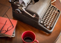 black retro typewriter sitting on wooden coffee table and cup of coffee, old worn books and stylish glasses are good for authors, writers, editors or journalists