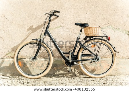 b5817fb8e3e Black retro vintage bicycle. Retro bicycle with basket in front of the old  wall.