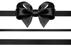 Black ribbon with gift bow isolated on white. Christmas festive bow of black shiny satin ribbon and horizontal lines of ribbon