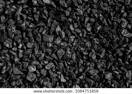 Black road stones gravel texture, rocks for construction, dark background of crushed granite gravel, small rocks, closeup