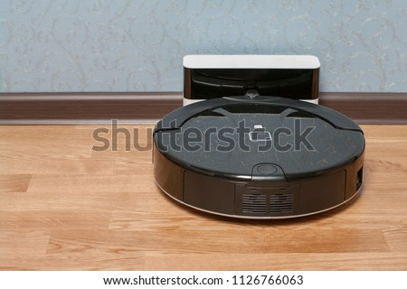 black Robot vacuum cleaner on charging dock after it is finished. Modern smart electronic housekeeping technology. Stock photo ©