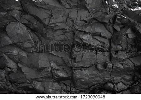 Black rock, stone, textured. Background for design. Hard light. stock photo