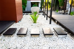 Black rocks walking way in tropical garden, Black stones garden path on white pebbles and lush green trees, Garden decoration concept.