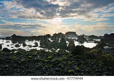 Black rocky volcanic coastline in a dramatic sunset, Pico island , Azores, Atlantic Ocean