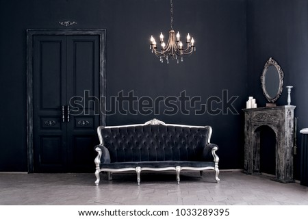 Black room in the castle with a vintage door, a chandelier, a sofa  and amirror and fireplace. Space where you can mount a person.