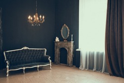 Black room in the castle with a window, a chandelier, a sofa and mirror and fireplace. Space where you can put a person.