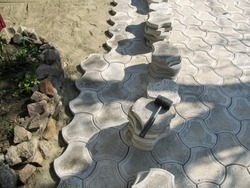 Black rubber hammer lies on a pile of paving slabs during its laying, background with copy space, top view. The concept of unfinished work on laying beautiful decorative figured paving tiles