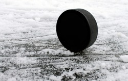 Black rubber hockey puck. With a place for text or images, isolated on snowy ice background. Fragment of ice hockey rink with. Concept hockey.