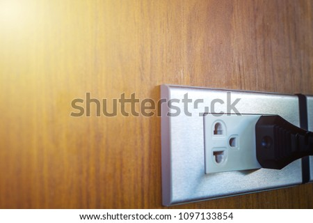 Black rubber plug power line is plugged into the power outlets on the wood wall. Flat sockets plug outlets on the wood wall with a plug power line. Sockets in Thailand with 220 volts (220V) AC style.