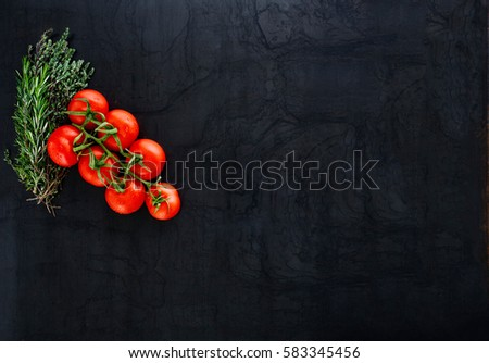 black rustic tabletop with branch of tomatoes and herbs, top view #583345456