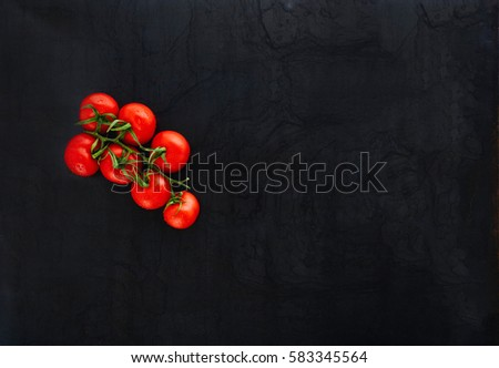 black rustic tabletop with branch of tomatoes, top view #583345564