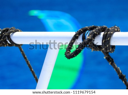 Black sailing ropes crossing in tie knots around boat white tube on blurred bokeh deep blue sea water background, picturesques abstraction eye catching picture for designs prome sail trips tourism #1119679154