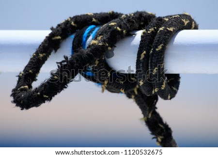 Black sailing ropes crossing in tie knots around boat white tube on blurred bokeh deep blue sea water background, picturesques abstraction eye catching picture for designs prome sail trips tourism #1120532675