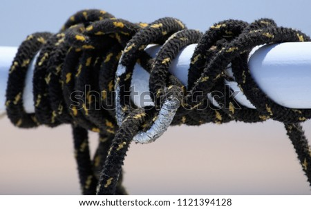 Black sailing ropes crossing in tie knots around boat white tube on blurred bokeh deep blue sea water background, picturesques abstraction eye catching picture for designs prome sail trips tourism  #1121394128