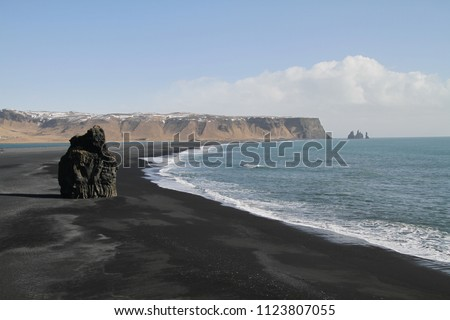 Black sand beach in Iceland, Dyrhólaey, Reynisfjara Beach. Rocks and cliffs at ocean beach. A popular tourist spot on the south coast of Iceland.