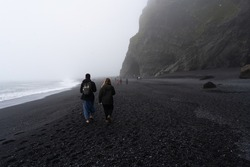 Black sand beach Vik Reynisfjara in Iceland with two tourists in the background