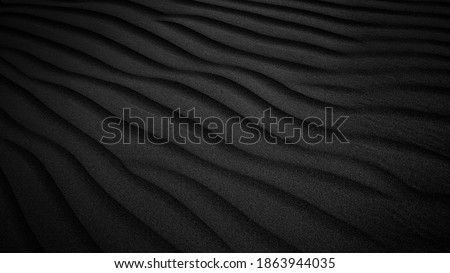Black Sand dune. Black Sand beach macro photography. Background, texture, wave pattern of oceanic sand on the beach, black. Texture of beach sand. Black beach.