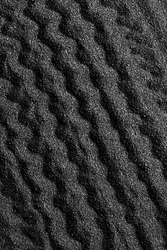 Black sand dunes background. Bump trace. Creative sand relief.