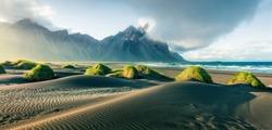 Black sand dunes on the Stokksnes headland on southeastern Icelandic coast with Vestrahorn (Batman Mountain). Picturesque summer panorama of Iceland, Europe. Instagram filter toned.