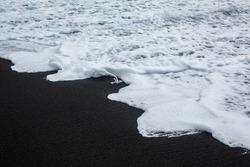 Black sand volcanic beach with white sea foam in Azores Islands. Ocean shorebreak pattern