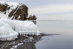 Black sand, winter beach, icicles, sea, rocks in the background, Tikhaya Bay, Sakhalin Island, Sea of Okhotsk
