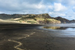 Black sand with yellow traces of dried sea foam on the Bathells Beach, rocks, white waves, cloudy sky, afternoon sun. Wintertime on the New Zealand's northern island