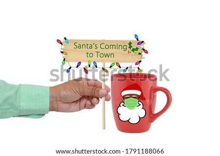 Black Santa Mug and Hand holding Santa's Coming sign  Foto stock ©