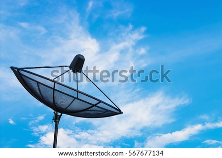 Black satellite dish or TV antennas on blue sky cloudy background.