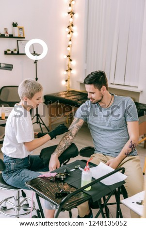 Black saturated ink . Short-haired blonde woman working with tattoo sleeve on her client hand #1248135052