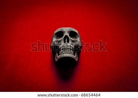 black scary human skull on red velvet background