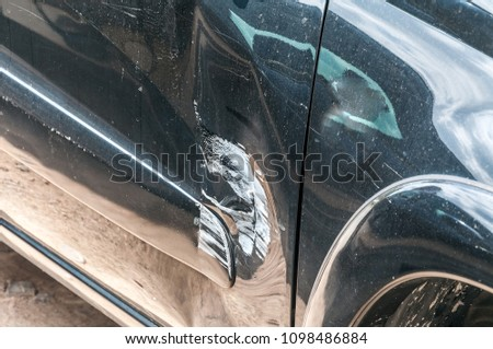 Black scratched car with damaged paint in crash accident on the street or collision on parking lot in the city with dented doors #1098486884