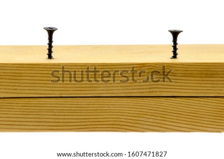 Black screws screwed into wood on white isolated background