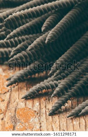 Black screws. Screws closeup. Screws on a rough wooden background. Fastener in construction. Construction details. Industrial background.