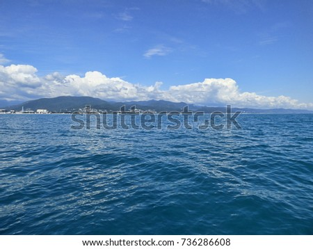 Black Sea coast - view from ship. Sunny summer day, clear water with small waves, town and mountains at the horizon. White clouds at deep blue sky. Natural background with place for text. #736286608