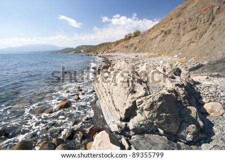 Black sea coastline with foam, transparent water, stones, pebbles and rocks against the blue sky with clouds #89355799