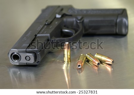 Black semi-automatic handgun with bullets, shallow depth of field