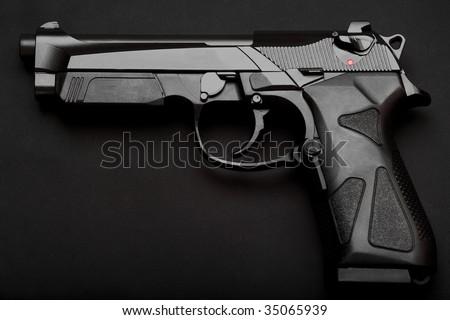 Black semi-automatic pistol on a black background