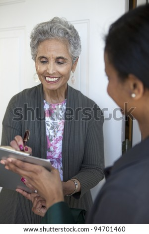 Black senior woman signs a petition at her front door