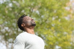 Black serious man breathing deeply fresh air in a park a sunny day with a green tree in the background