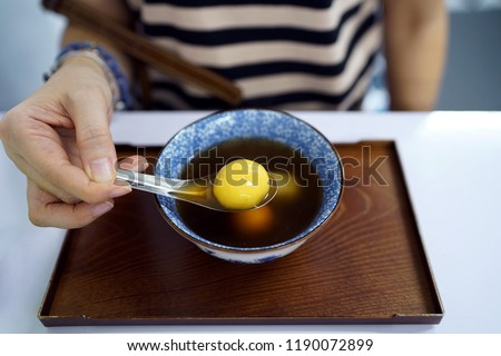 Black sesame dumplings (Tangyuan) served in ginger tea, Sticky rice balls with grounded black sesame inside, A favorite healthy dessert, Chinese dessert that is popular in Thailand.