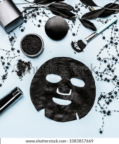 Black sheet mask and cosmetic products setting with Activated Charcoal, top view. Beauty and modern skin care concept. Branding mock up