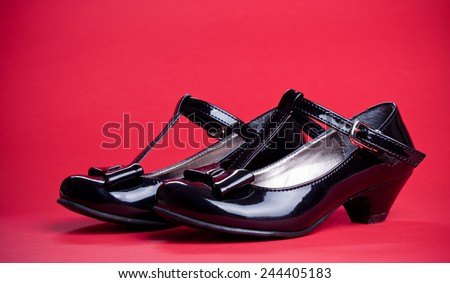 Black shine leather girl shoes with black ribbon isolated on red