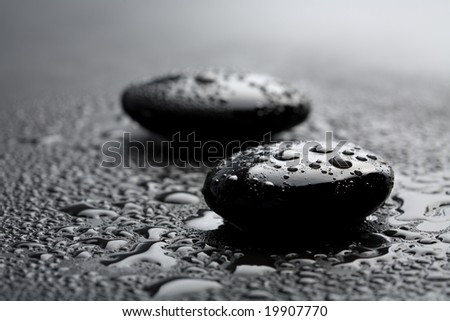 black shiny zen stones with water drops over black background